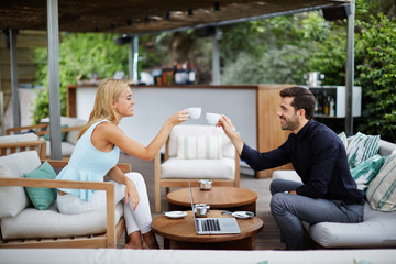 Business partners smiling while drinking coffee and talking abou