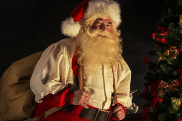 Santa Claus carrying huge sack with presents