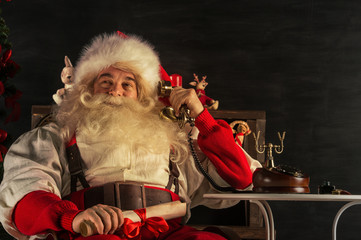 Portrait of emotional Santa Claus calling phone at home