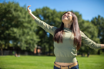 Young Asian Woman feeling happy refreshed in a park
