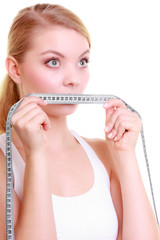 Fitness girl fit woman covering her mouth with measuring tape