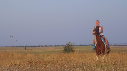 Horseback riding through the field in countryside