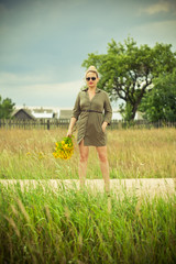 girl in a green dress standing with a bouquet of yellow flowers