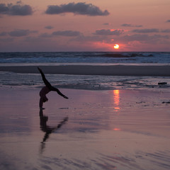 silhouetted gymnast dong handstand on beach in sunset light