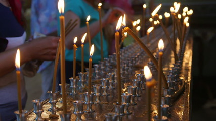 Faithful people lighting prayer candles in the church c