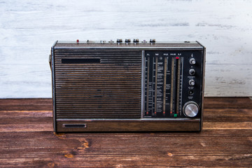An old dark brown radio on wood table.