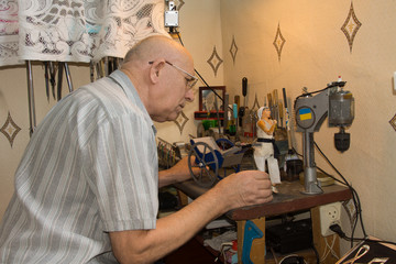 Elderly man building a model of a girl and cart
