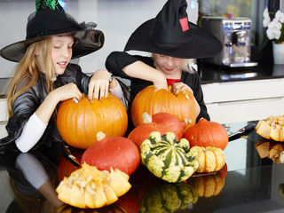 Two witches with pumpkins in the kitchen