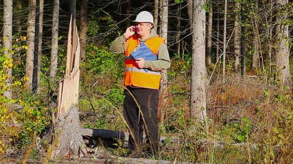 Lumberjack talking on cell phone in destroyed forest