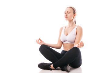 Young woman sitting in lotus position isolated