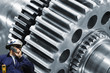 engineer with large cogwheel and gears machinery