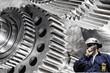 engineer, worker with cogwheels machinery, steel and titanium