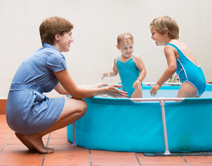 Children and mother playing in pool