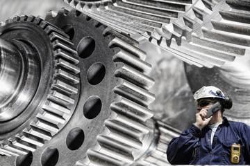 engineer, worker with cogwheels machinery, steel and titanium