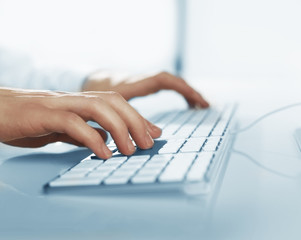 hands pushing keys of computer