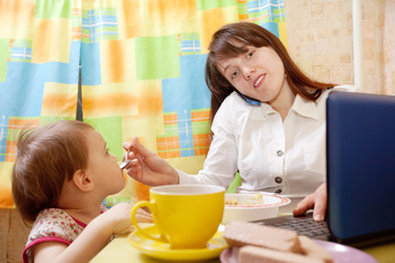 businesswoman feeding baby and  using  latop