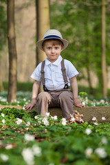 Outdoor portrait of a boy wearing hat and suspenders