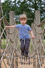 Little boy climbing a rope bridge at playground.
