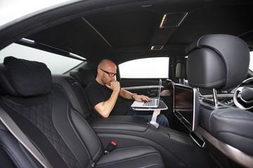 online im Fond einer Limousine