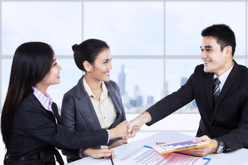 Business partners shaking hands at meeting