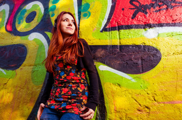 young redhead woman at colorful graffiti wall