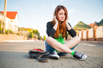 young redhead woman listening music at uptown street