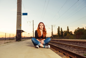 young redhead woman at old railway station