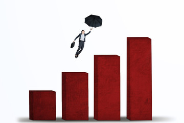 Businesswoman flying with umbrella over graph isolated