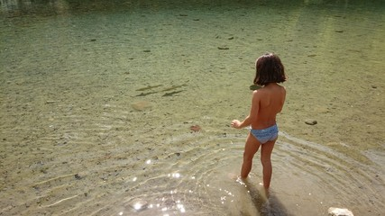 Niña intentando coger peces en el río