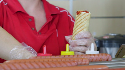 Employee prepares  hotdog in fast food takeaway restaurant