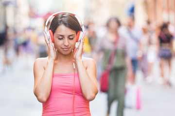 Beautiful Young Woman Listening Music in the City