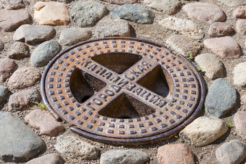 Old steel sewer manhole on the cobblestone road. Text on russian