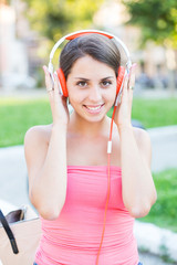 Beautiful Girl with Headphones Listening Music at Park