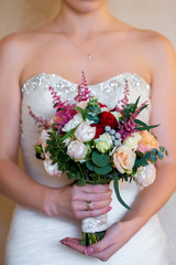 Bride holding a wedding bouquet of pink roses.