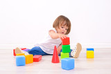 Fototapety little girl playing with colored cubes