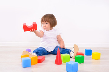 little girl playing with colored cubes