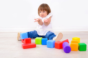 little girl playing with colorful cubes