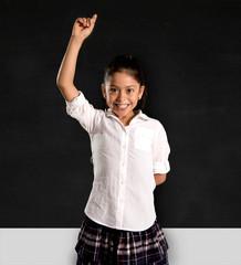 Hispanic schoolgirl rising hand up to answer teacher