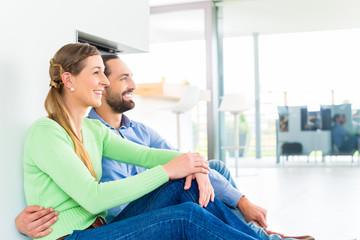 Paar sitzt im Wohnzimmer am Kamin