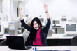 Successful businesswoman with arms up