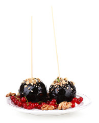 Sweet caramel apples on sticks with berries, isolated on white