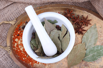White round bowls of bay leaves and seasoning scattered