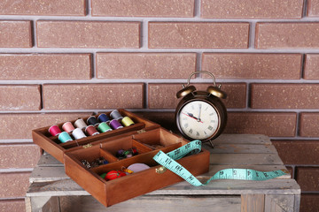 Sewing kit with tapeline on a wooden box in front of brick wall