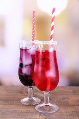 Glasses of cold berry cocktail on wooden table