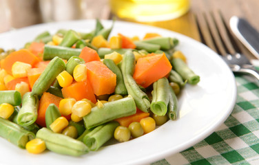 Delicious vegetables salad on plate on table close-up