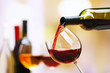 Leinwandbild Motiv Red wine pouring into wine glass, close-up