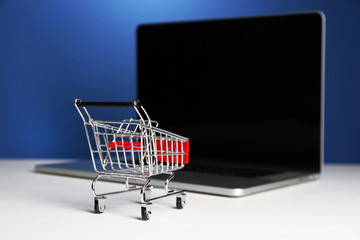 Shopping cart on laptop on table, on blue background