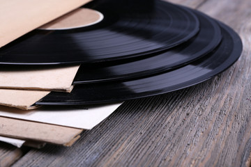 Vinyl records records and paper covers on wooden background