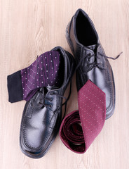 Black man's shoes, pair of socks and tie on wooden background