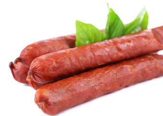 Smoked thin sausages  with basil leaves, isolated on white